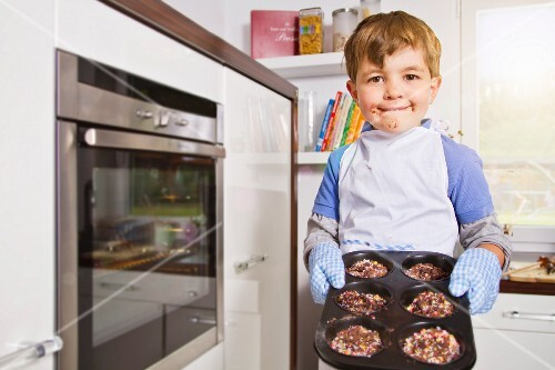 Germany, Boy baking cup cakes in tray, portrait