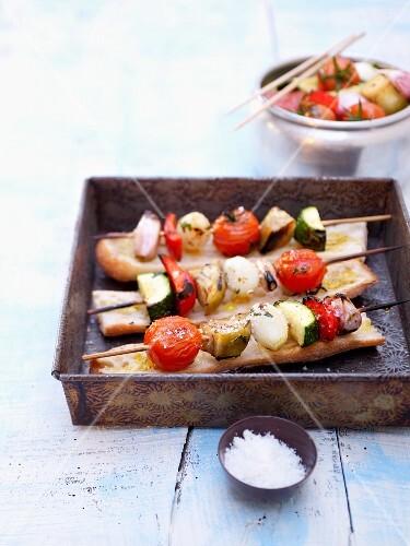 Grilled vegetable kebabs on bread
