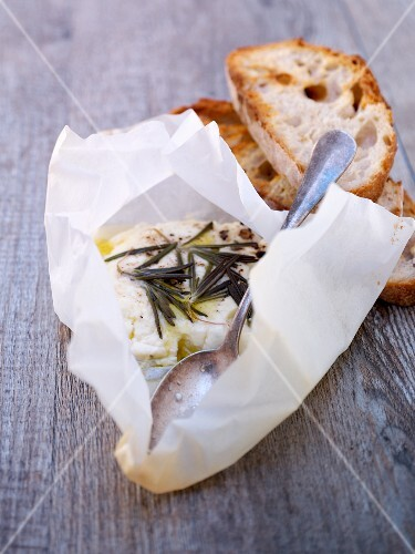 Goat cheese with rosemary and olive oil in parchment paper