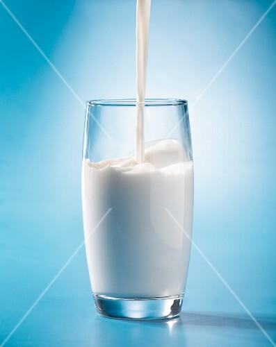 Milch fließt in ein Glas
