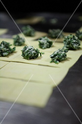 Raw squares of pasta dough, with spinach and ricotta mixture