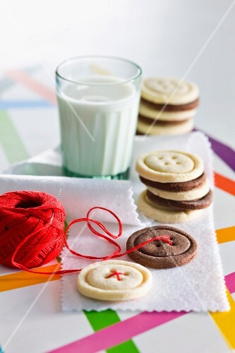 Button-shaped biscuits and a glass of milk