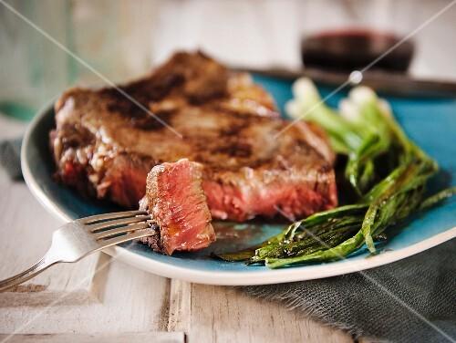 Dry-Aged Rib-Eye Steak with Green Onions; Piece of Steak Pierced on Fork