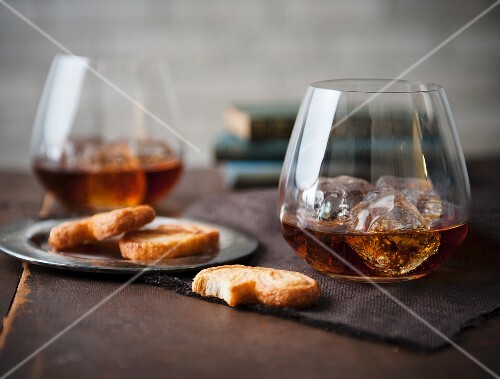 Two Stemless Glasses of Whisky on the Rocks with Cookies