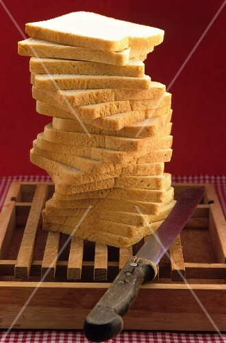 Sliced bread, stacked, with a knife