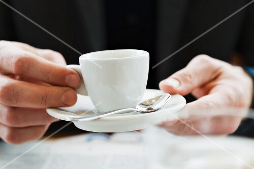 Hands holding an espresso cup