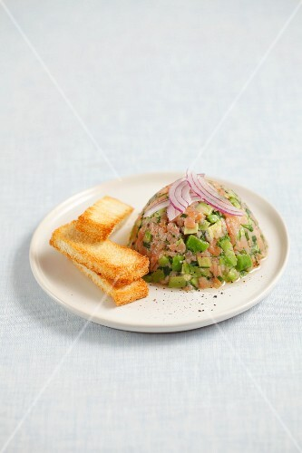 Smoked salmon and avocado tartar topped with onions and served with toast