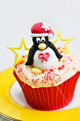 Christmas cupcake with an iced penguin on top with stars