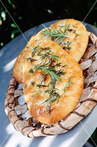 two Italian foccacia breads outside on a wooden tray