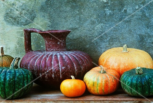 old terracotta jug with orange and green pumpkins