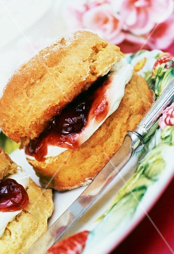 a scone filled with jam and cream on a plate with knife