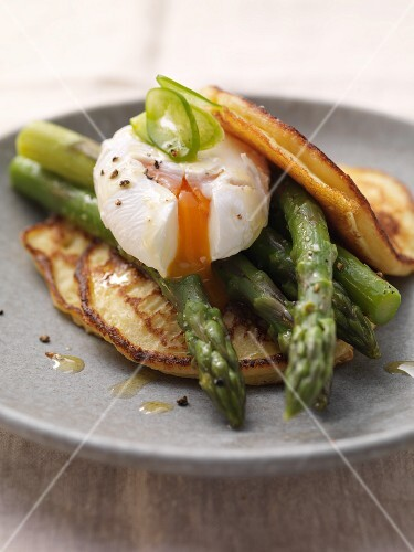 Pancakes topped with asparagus and a poached egg