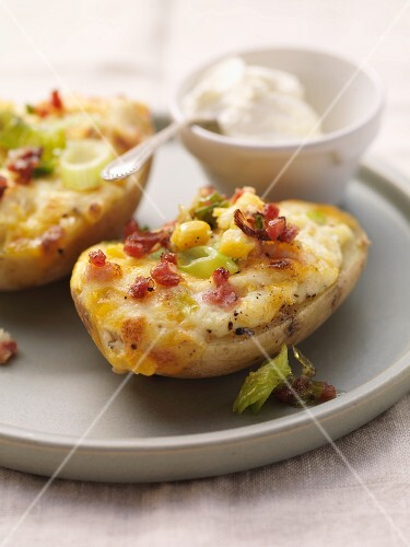 Baked potatoes topped with cheese, bacon and sweetcorn