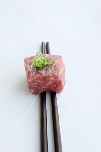 Wagyu beef on chopsticks with sliced spring onions (Negi)