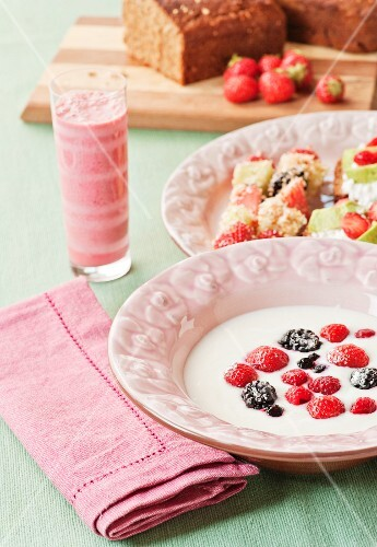 A Swedish breakfast of berries in sour milk, fruit and coconut skewers and raspberry and kiwi smoothies