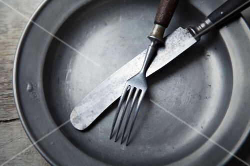 A tin plate with silver cutlery