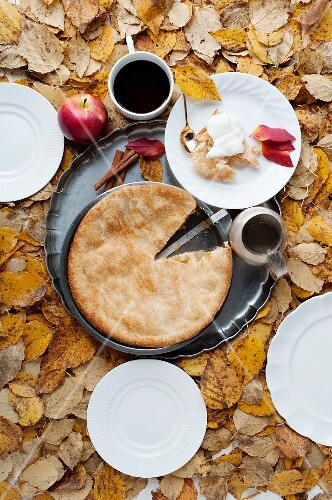 An apple pie and a mug of coffee surrounded by autumn leaves