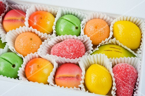 a box of coloured yellow, green, orange and red marzipan fruit sweets for Christmas