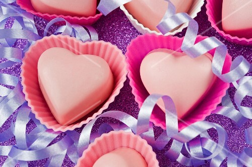 pink love heart shaped chocolates in pink cake covers with purple party streamers on a purple glittery table top