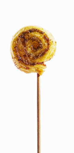 A wooden skewer topped with a puff pastry whirl with pesto
