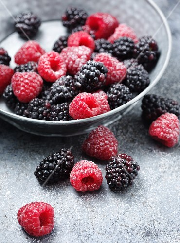 Sugared raspberries and blackberries in and in front of a bowl