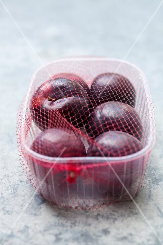 Several plums in a plastic pot wrapped in netting