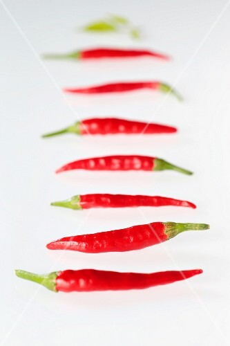 Several fresh red chillies in a line