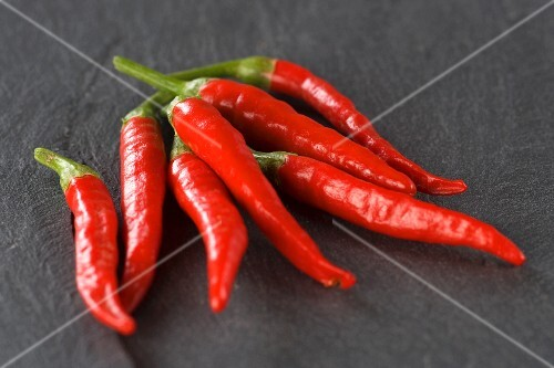 Several fresh red chillies on a slate slab