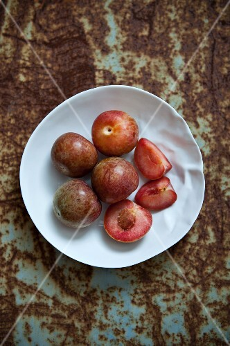 Fresh plums, whole and cut into pieces, on a plate
