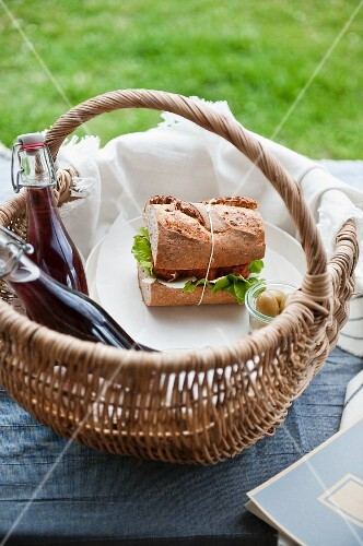 A picnic basket with a sandwich and drinks