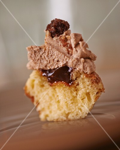 A cupcake topped with chocolate cream, cut in half