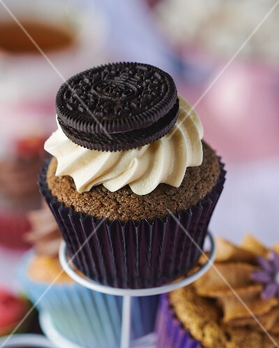 A chocolate cupcake topped with cream and a biscuit
