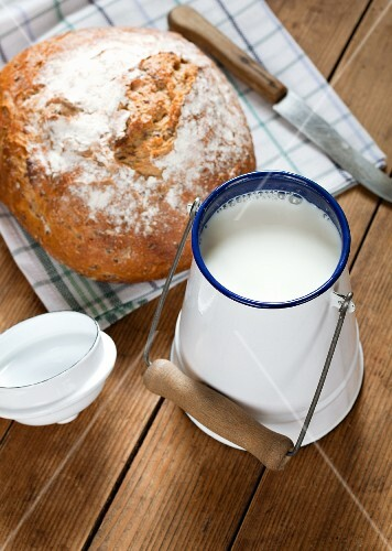 A fresh loaf of bread and a can of milk