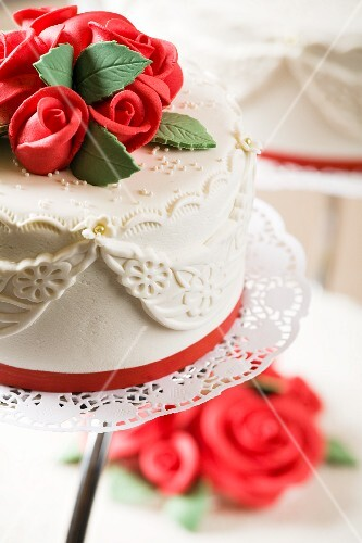 A wedding cake with red marzipan roses