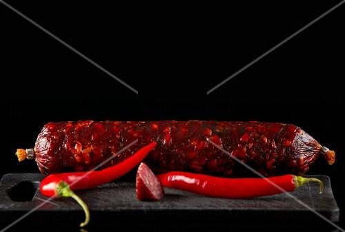 Salami sausage and chili on old black plastic cutting board