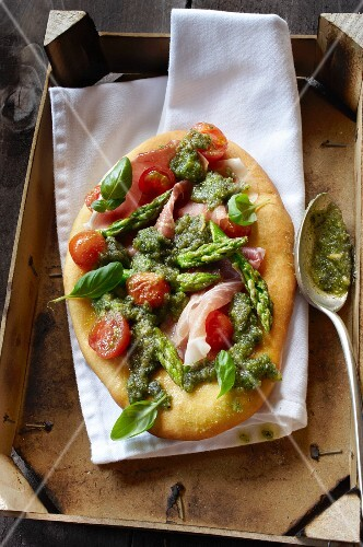 Pizza topped with green asparagus and tomatoes