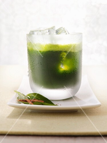 A glass of spinach and melon juice with ice cubes