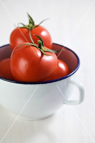 Several tomatoes in an enamel cup
