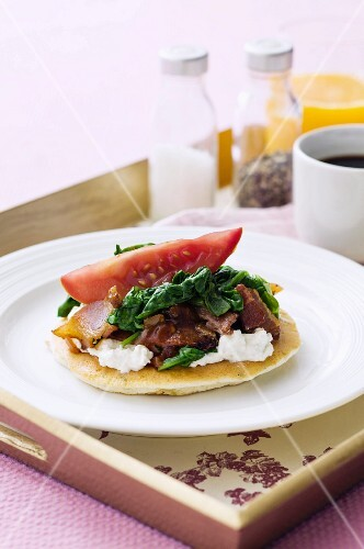 A pancake topped with ricotta, spinach and pancetta, for breakfast