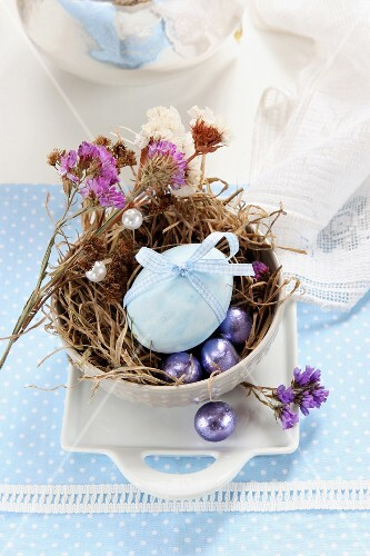 An egg decorated with a ribbon, dried flowers and chocolate eggs in an Easter nest made of moss and grass
