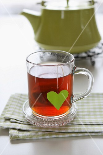 A glass cup of wellness tea and a teabag with a heart