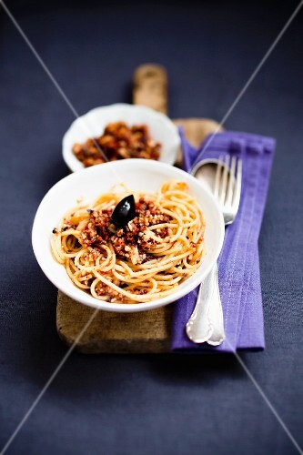 Spaghetti with red pesto with an olive on top