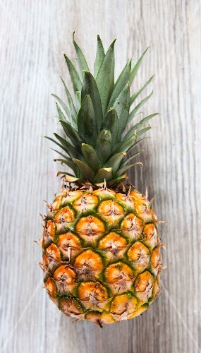 A pineapple on a wooden slap, viewed from above