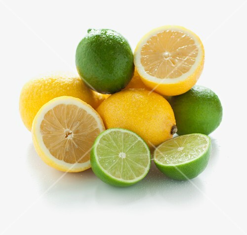 A pile of limes and lemons, whole and halved