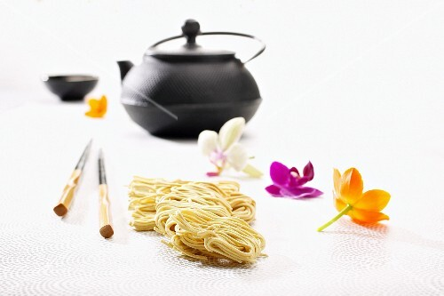 Egg noodles, chopsticks, a teapot and orchid flowers