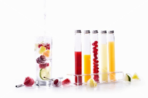 A glass of water with fruits in, and frozen fruits and juices in glass tubes