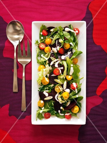 Mixed Green Salad with Red and Yellow Cherry Tomatoes and a Creamy Dressing; On a Serving Platter with Serving Spoon and Fork