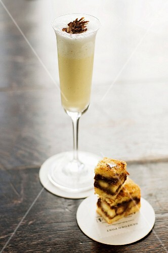 A Milkshake in a Champagne Flute with Small Chocolate Nut Sandwich Squares