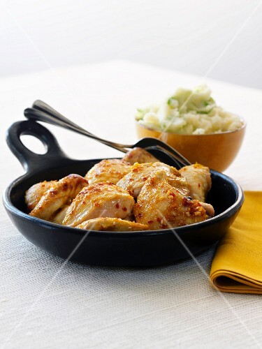 Honey Glazed Chicken in a Cast Iron Skillet; Bowl of Mashed Potatoes in the Background