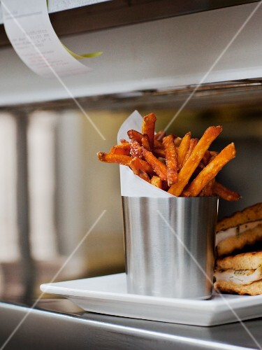 "Seasoned Fries with Wax Paper in a Steel Cup on a Restaurant ""Order-Up"" Counter"